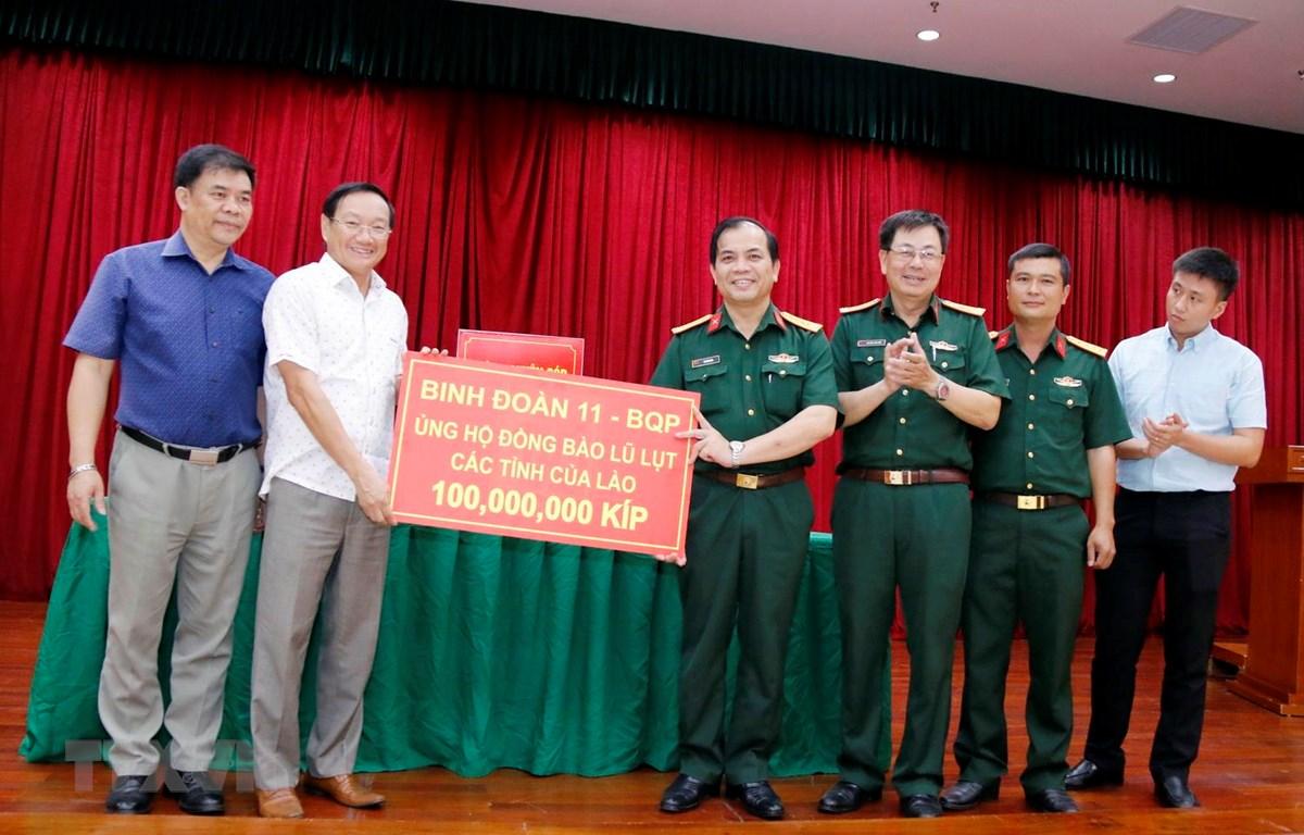 Đại diện Binh đoàn 11 thuộc Bộ Quốc phòng Việt Nam, trao số tiền ủng hộ 100 triệu kíp (hơn 11.000 USD). (Ảnh: Phạm Kiên/TTXVN)