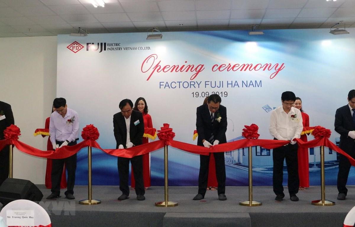 Các đại biểu thực hiện nghi lễ cắt băng khánh thành Nhà máy Fuji Electric. (Ảnh: Nguyễn Chinh/TTXVN)