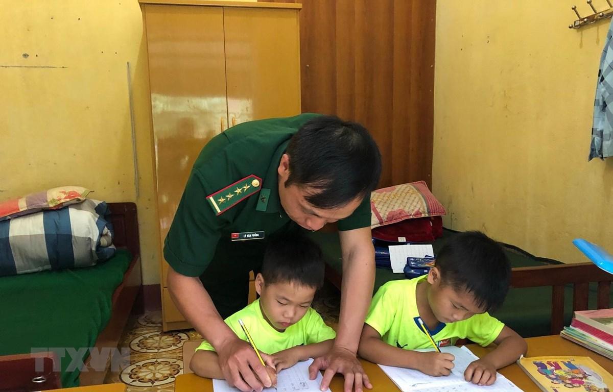 """Cán bộ đồn biên phòng Xuân Trường dạy các """"con nuôi"""" học bài. (Ảnh: Chu Hiệu/TTXVN)"""