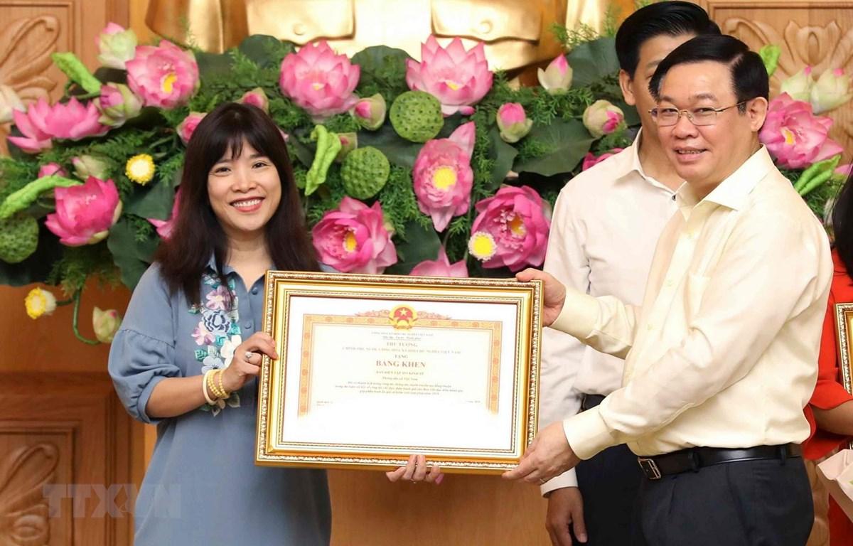 Phó Thủ tướng Vương Đình Huệ trao tặng Bằng khen của Thủ tướng Chính phủ cho tập thể Ban biên tập tin Kinh tế thuộc Thông tấn xã Việt Nam đã có thành tích xuất sắc đột xuất trong công tác điều hành giá năm 2018. (Ảnh: Văn Điệp/TTXVN)