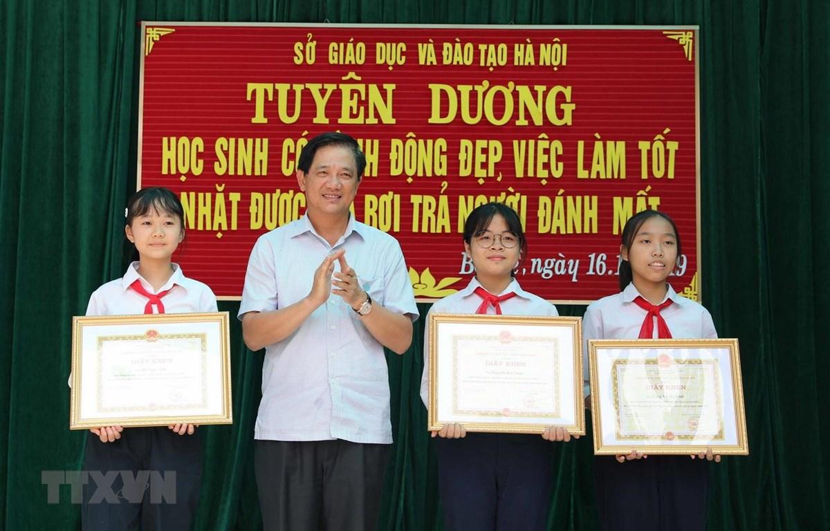 Phó Giám đốc Sở Giáo dục và Đào tạo Hà Nội Phạm Xuân Tiến trao Giấy khen của Giám đốc Sở cho 3 học sinh. (Ảnh: Thanh Tùng/TTXVN)