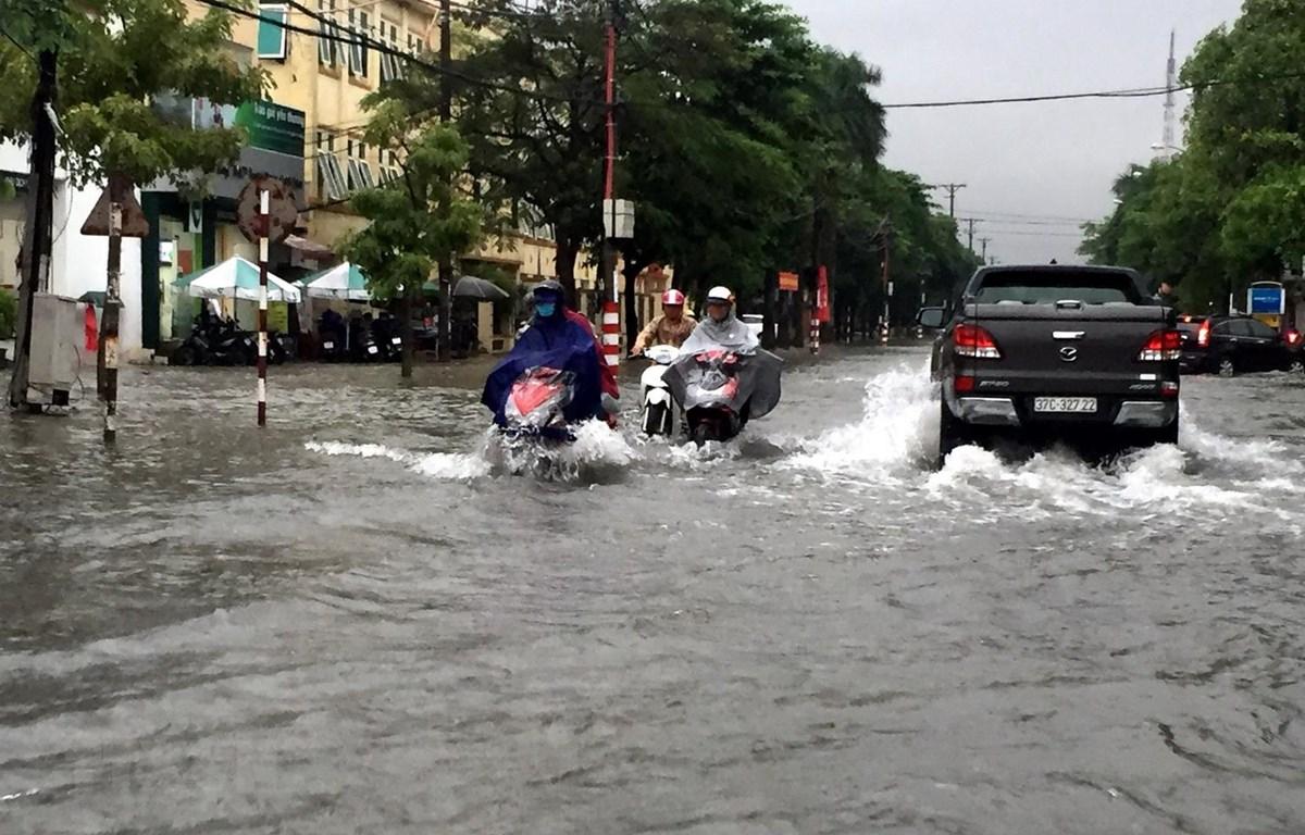 Nhiều tuyến đường thành phố Vinh bị ngập khiến các phương tiện tham gia giao thông gặp nhiều khó khăn. (Ảnh: Tá Chuyên/TTXVN)