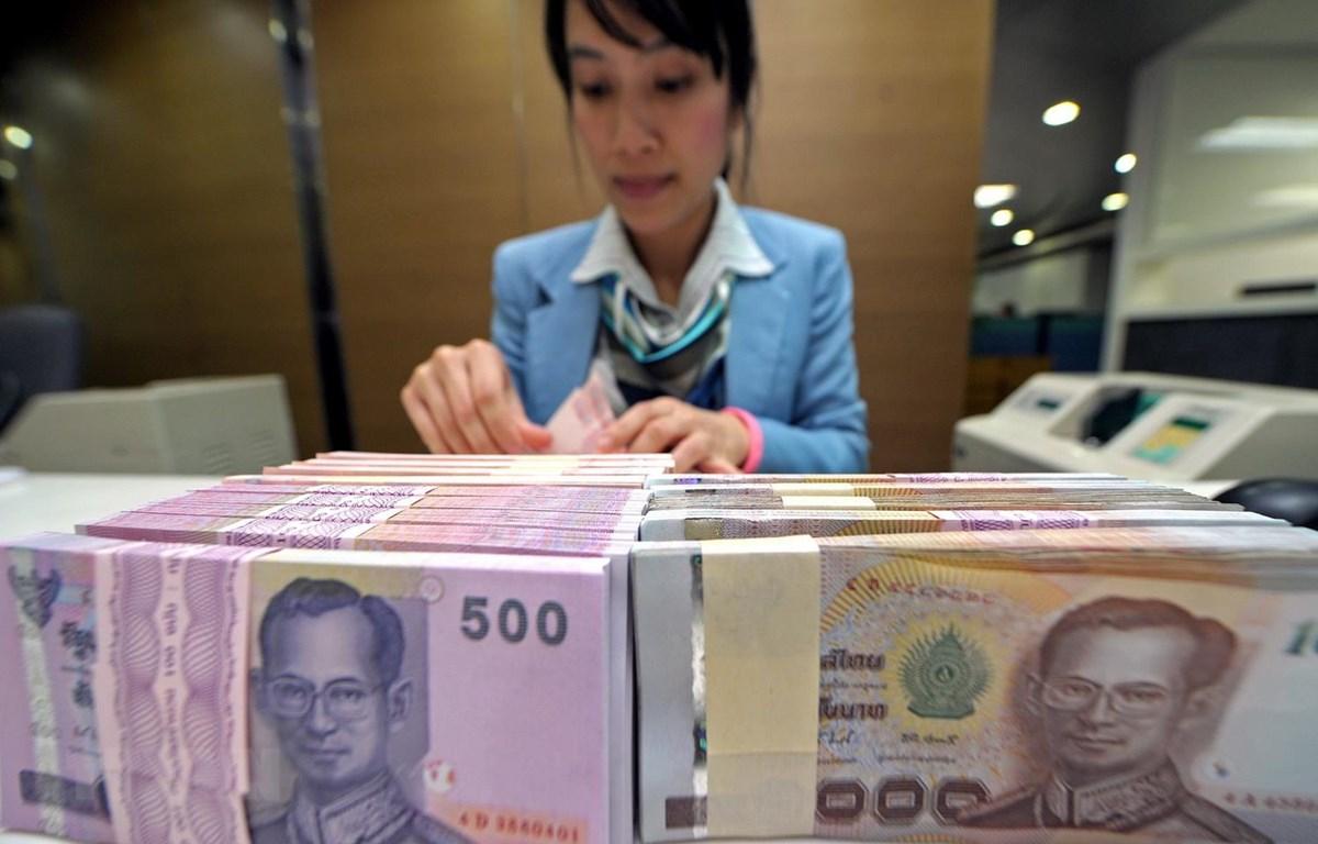 Kiểm đồng baht tại ngân hàng Krung Thai ở Bangkok của Thái Lan. (Ảnh: AFP/TTXVN)