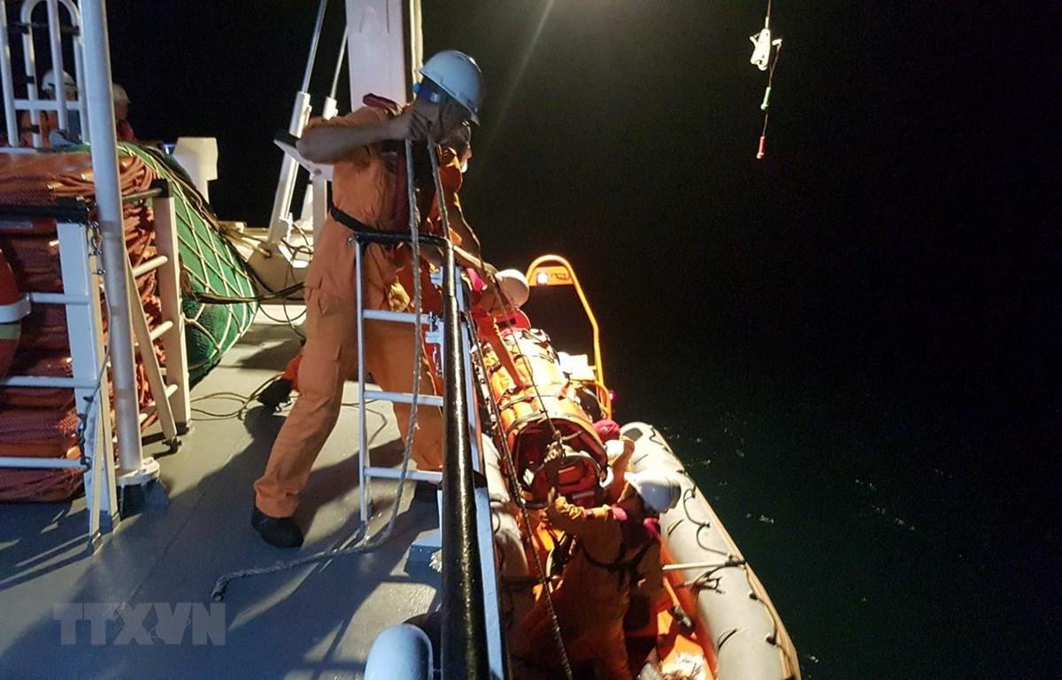 Xuồng cứu nạn của tàu SAR 412 đưa ngư dân bị nạn lên tàu SAR 412 để cấp cứu và chuyển về bờ. (Ảnh: TTXVN phát)