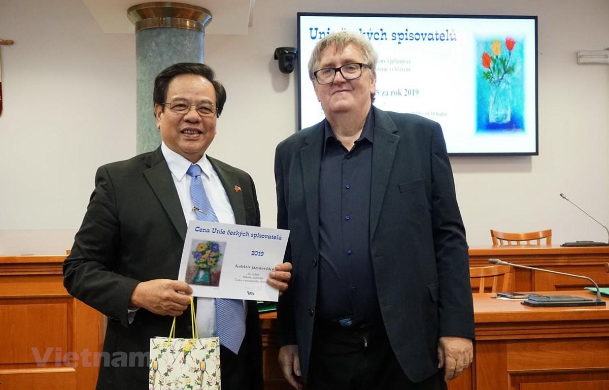 Tác giả Nguyễn Quyết Tiến nhận giải thưởng. (Ảnh: Hồng Kỳ/Vietnam+)