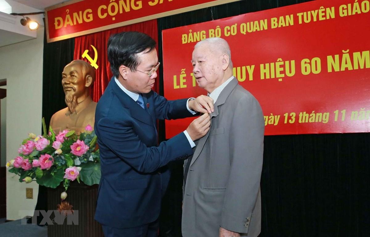 Trưởng Ban Tuyên giáo Trung ương Võ Văn Thưởng gắn Huy hiệu 60 năm tuổi Đảng cho đồng chí Lê Xuân Tùng. (Ảnh: Doãn Tấn/TTXVN)