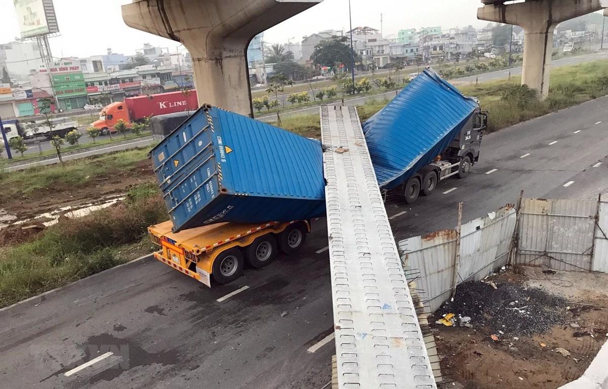Xe container bị dầm bêtông đè lên dập móp. (Ảnh: TTXVN phát)