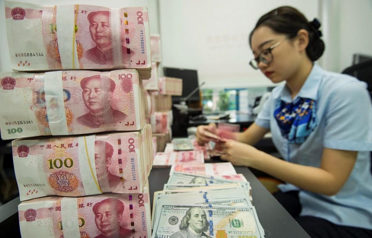 Kiểm đồng 100 nhân dân tệ tại ngân hàng ở tỉnh Giang Tô của Trung Quốc. (Ảnh: AFP/TTXVN)