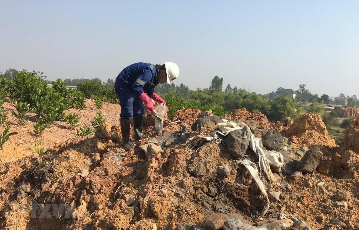 Viện Khoa học và Công nghệ Môi trường lấy mẫu để phân tích thành phần có trong chất thải bị đổ trộm tại thôn Lai Thôn, xã Bắc Sơn, huyện Sóc Sơn, Hà Nội. (Ảnh: Mạnh Khánh/TTXVN)