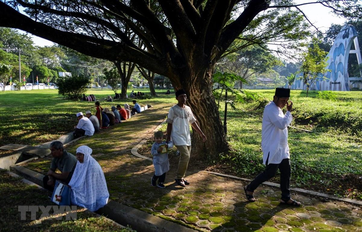 Người dân tập trung tại nghĩa trang quận Aceh Besar, tỉnh Aceh ở Indonesia ngày 26/12, để tưởng niệm các nạn nhân thiệt mạng trong thảm họa động đất-sóng thần 15 năm trước. (Ảnh: AFP/TTXVN)