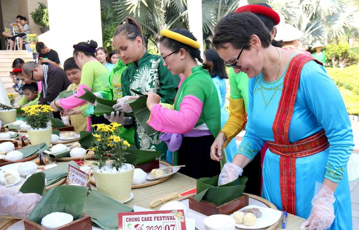 Du khách quốc tế hào hứng gói bánh chưng và trải nghiệm không gian Tết Việt. (Ảnh: Nguyễn Thanh/TTXVN)