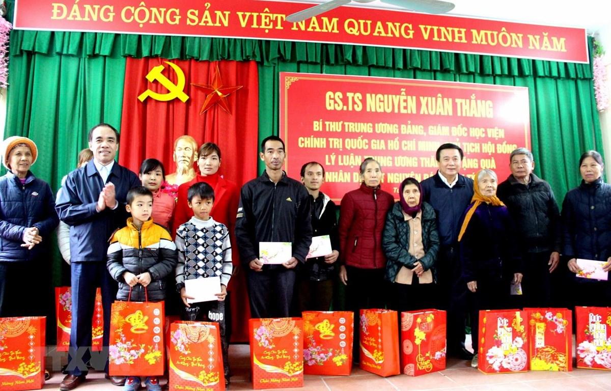 Ông Nguyễn Xuân Thắng trao quà cho các hộ nghèo, gia đình chính sách xã Tân Tiến. (Ảnh: Quang Cường/TTXVN)