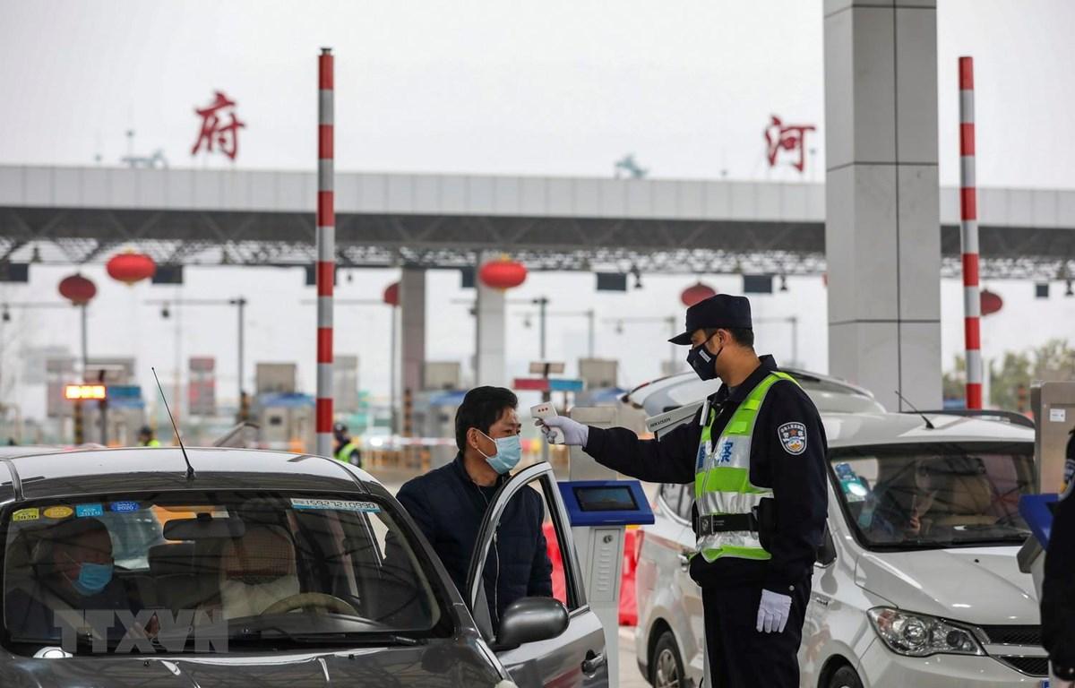 Kiểm tra thân nhiệt của lái xe trên tuyến đường cao tốc ở Vũ Hán, tỉnh Hồ Bắc, Trung Quốc, ngày 24/1. (Ảnh: AFP/TTXVN)