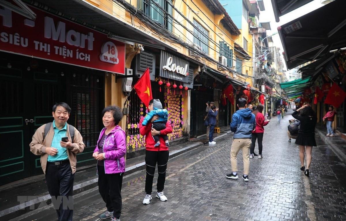 Khách du lịch quốc tế trải nghiệm không khí sáng mùng 1 Tết tại phố Tạ Hiện. (Ảnh: Thành Đạt/TTXVN)