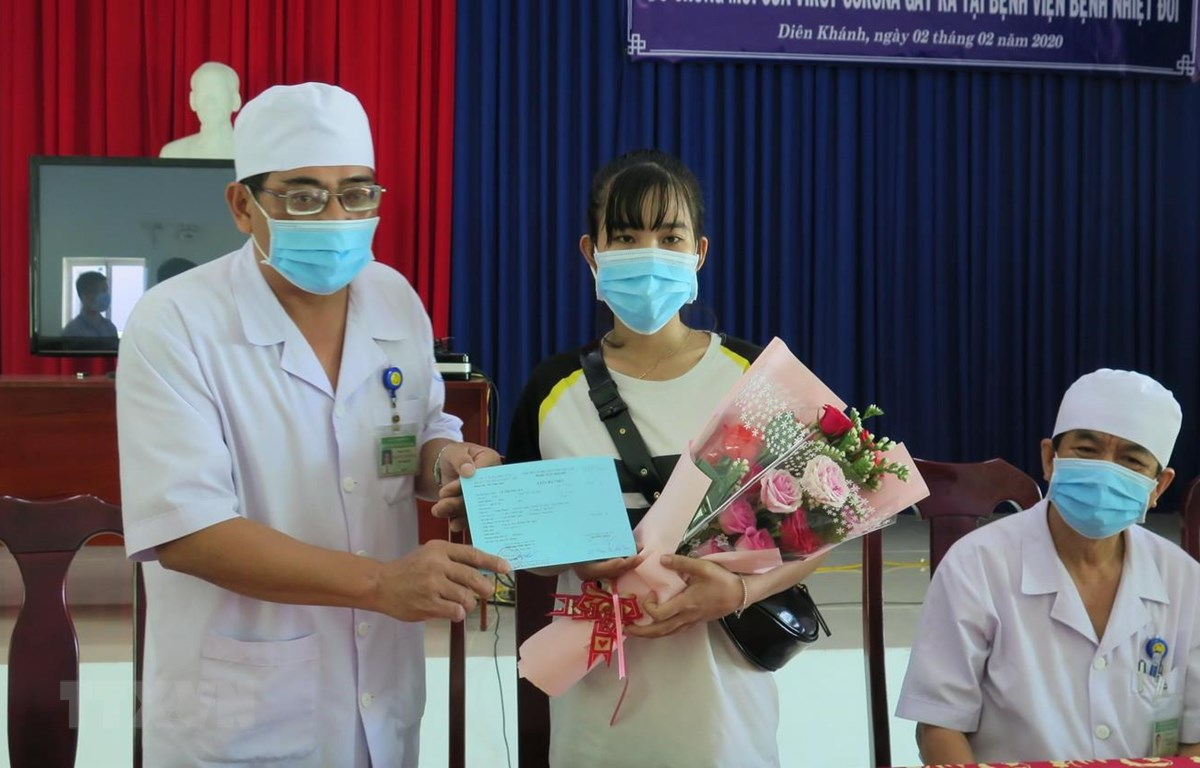 Phó Giám đốc Bệnh viện Bệnh Nhiệt đới Khánh Hòa Nguyễn Vũ Quốc Bình tặng hoa và trao giấy xuất viện cho bệnh nhân Lê Thị Thu H. (Ảnh: Phan Sáu/TTXVN)