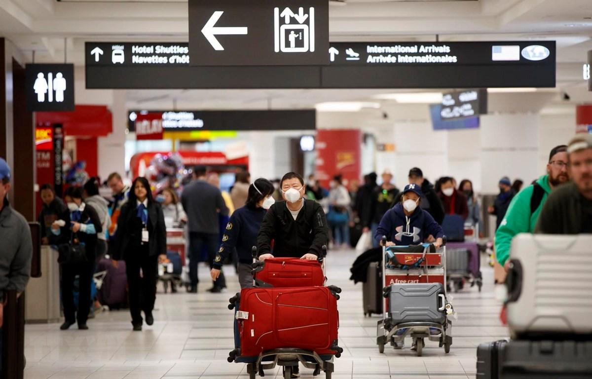 Hành khách đeo khẩu trang đề phòng lây nhiễm virus corona tại sân bay quốc tế Toronto Pearson, Canada, ngày 26/1 vừa qua. (Ảnh: AFP/TTXVN)