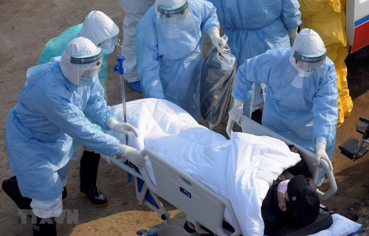 Nhân viên y tế hỗ trợ bệnh nhân nhiễm COVID-19 gây bệnh viêm đường hô hấp cấp (thứ 2, trái) tới bệnh viện dã chiến ở Vũ Hán, tỉnh Hồ Bắc, Trung Quốc ngày 4/2 vừa qua. (Ảnh: THX/TTXVN)