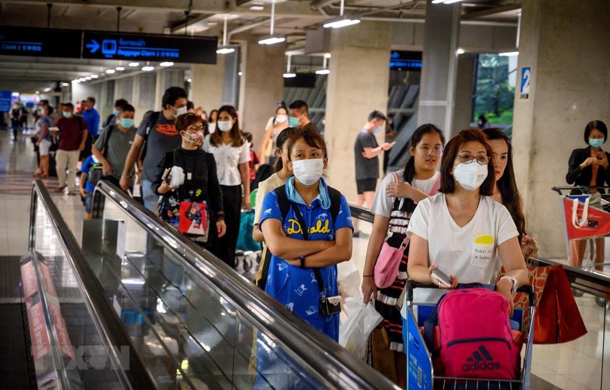 Hành khách đeo khẩu trang phòng lây nhiễm bệnh viêm đường hô hấp cấp COVID-19 tại sân bay ở Bangkok, Thái Lan. (Ảnh: AFP/TTXVN)