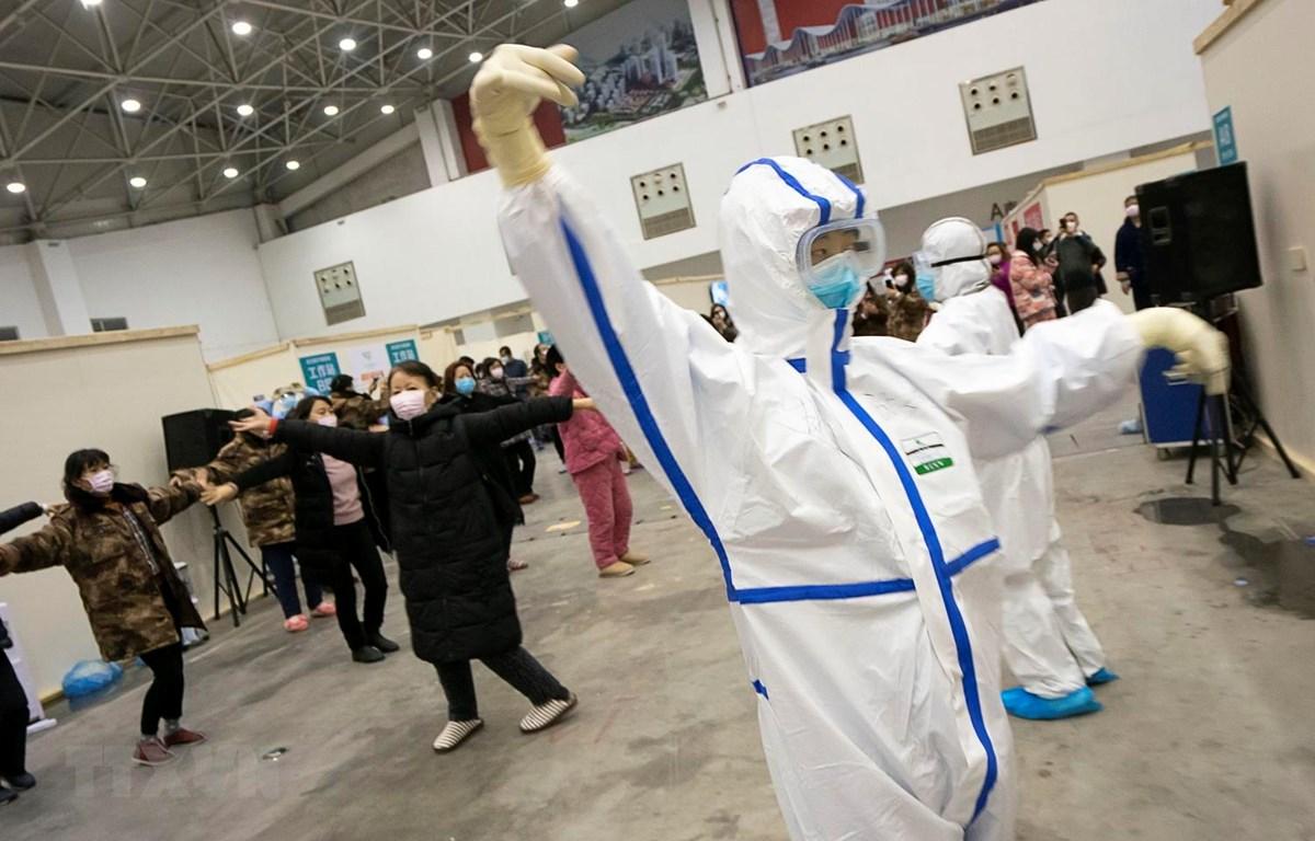 Các bệnh nhân tham gia tập thể dục dưới sự hướng dẫn của nhân viên y tế tại bệnh viện dã chiến ở Vũ Hán, tỉnh Hồ Bắc, Trung Quốc, ngày 12/2 vừa qua. (Ảnh: THX/TTXVN)