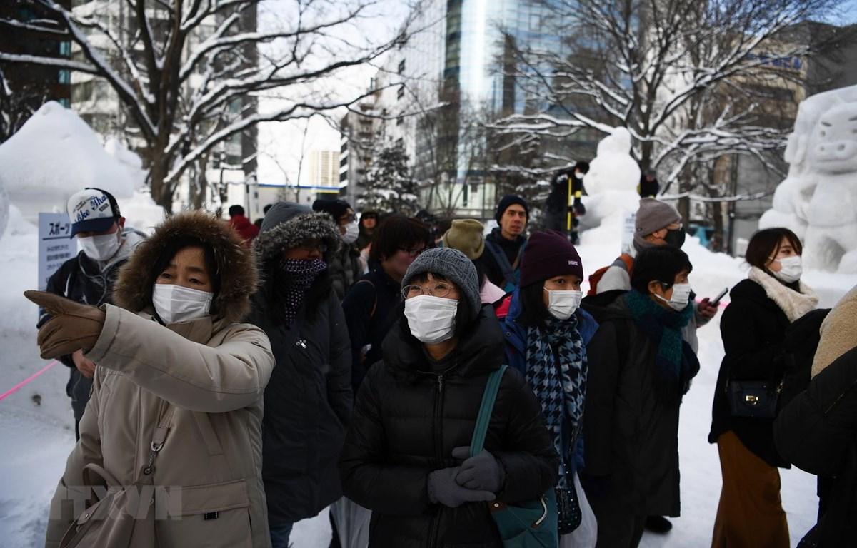 Khách du lịch đeo khẩu trang đề phòng lây nhiễm dịch COVID-19 khi thăm quan lễ hội tuyết thường niên tại thành phố Sapporo, Nhật Bản ngày 4/2 vừa qua. (Ảnh: AFP/TTXVN)