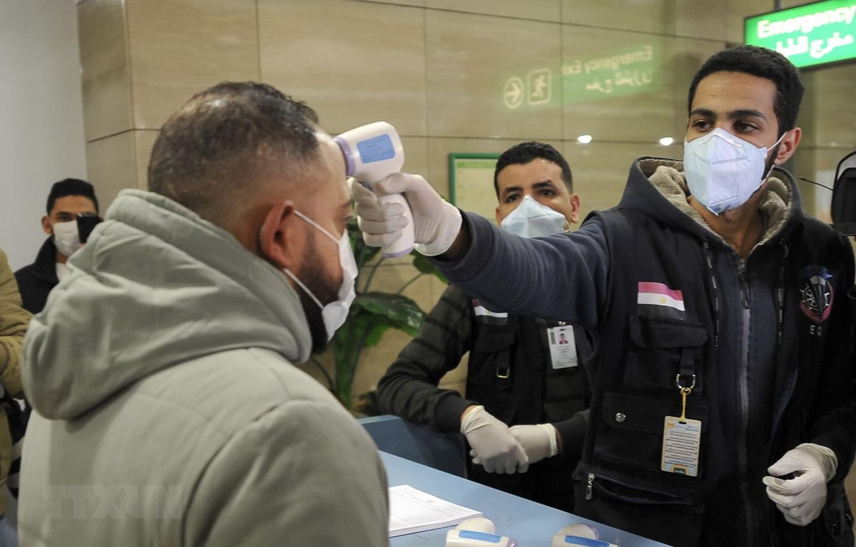 Nhân viên Cơ quan kiểm dịch Ai Cập kiểm tra thân nhiệt hành khách nhằm ngăn ngừa dịch viêm đường hô hấp cấp COVID-19 tại sân bay quốc tế Cairo. (Ảnh: AFP/TTXVN)