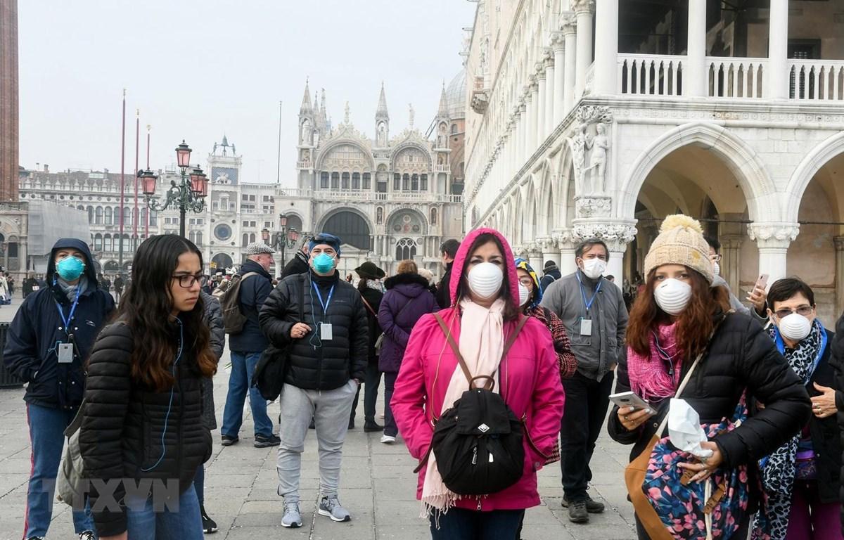 Người dân và khách du lịch đeo khẩu trang phòng tránh dịch COVID-19 tại Venice, Italy, ngày 25/2 vừa qua. (Ảnh: AFP/TTXVN)