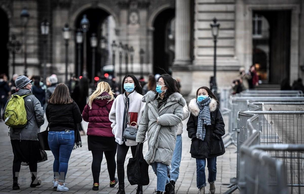 Người dân và du khách đeo khẩu trang phòng tránh lây nhiễm COVID-19 tại Paris, Pháp. (Ảnh: AFP/TTXVN)