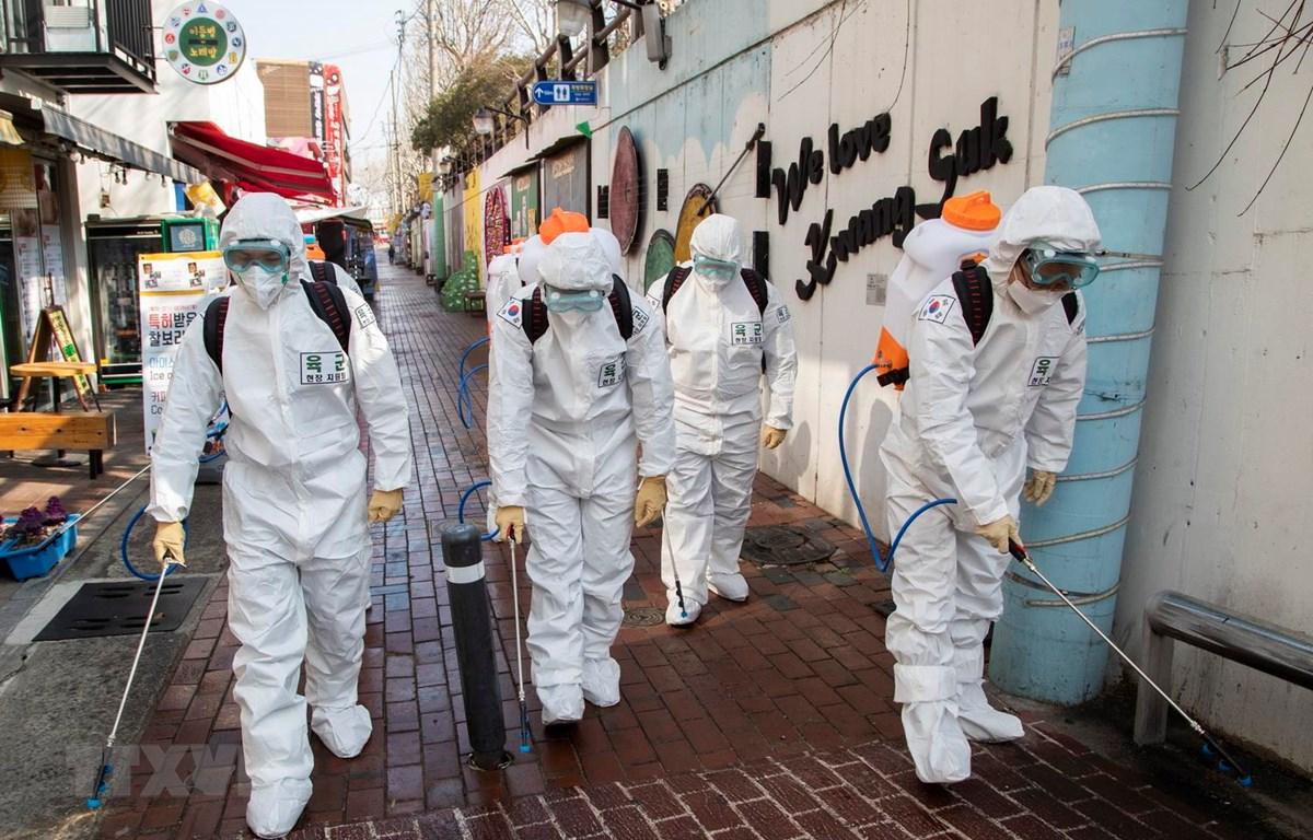 Binh sỹ Hàn Quốc mặc trang phục bảo hộ phun khử trùng một tuyến phố ở thành phố Daegu ngày 5/3 vừa qua. (Ảnh: THX/TTXVN)