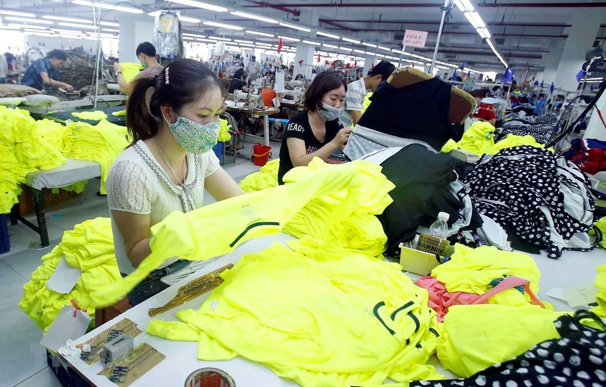Công nhân sản xuất sản phẩm may mặc. (Ảnh: Phạm Kiên/TTXVN)
