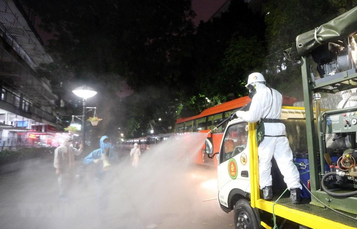 Lực lượng bộ đội hóa học phun hóa chất khử trùng, tẩy độc Bệnh viện Bạch Mai. (Ảnh: Dương Giang/TTXVN)