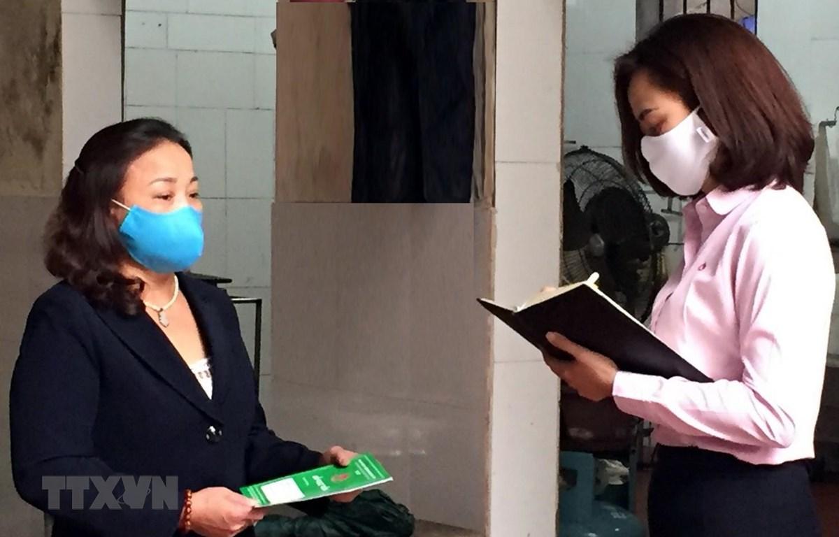 Nhân viên tín dụng Ngân hàng Chính sách Xã hội quận Nam Từ Liêm kiểm tra hộ vay bị ảnh hưởng bởi dịch COVID-19 để có những giải pháp thích hợp. (Ảnh: Trần Việt/TTXVN)