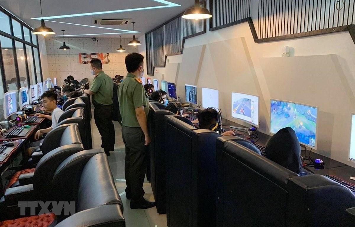 Lực lượng chức năng kiểm tra, bắt quả tang hàng chục thanh thiếu niên chơi game tại cơ sở kinh doanh Internet Pôn Gaming. (Ảnh: TTXVN) phát