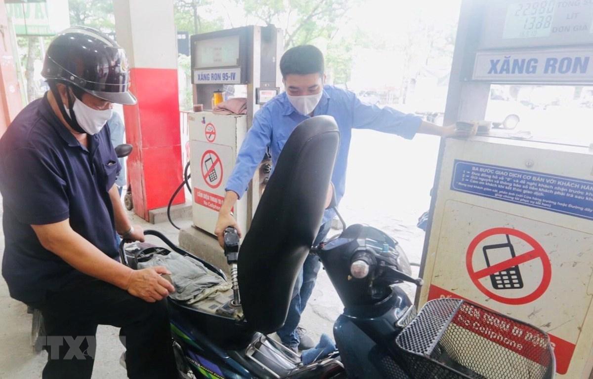 Mua bán xăng dầu tại một điểm kinh doanh của Petrolimex. (Ảnh: Trần Việt/TTXVN)