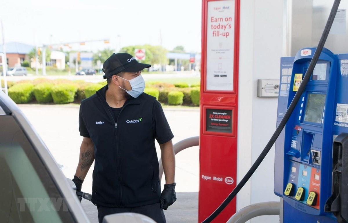 Nhân viên bơm xăng cho phương tiện tại một trạm xăng ở Plano, bang Texas, Mỹ ngày 20/4 vừa qua. (Ảnh: THX/TTXVN)