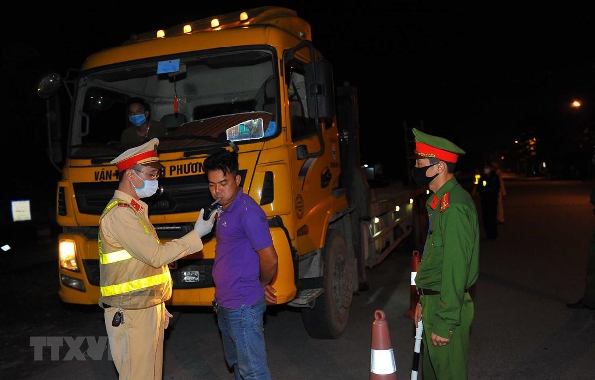 Lực lượng chức năng kiểm tra nồng độ cồn của chủ các phương tiện tham gia giao thông. (Ảnh: Minh Đức/TTXVN)