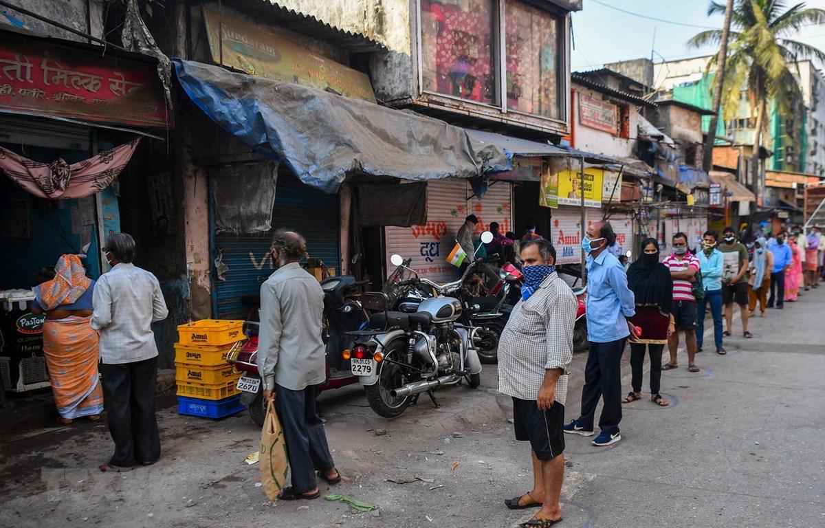 Người dân xếp hàng lấy sữa tại khu ổ chuột Dharavi ở Mumbai, Ấn Độ, ngày 6/4 vừa qua. (Ảnh: AFP/TTXVN)