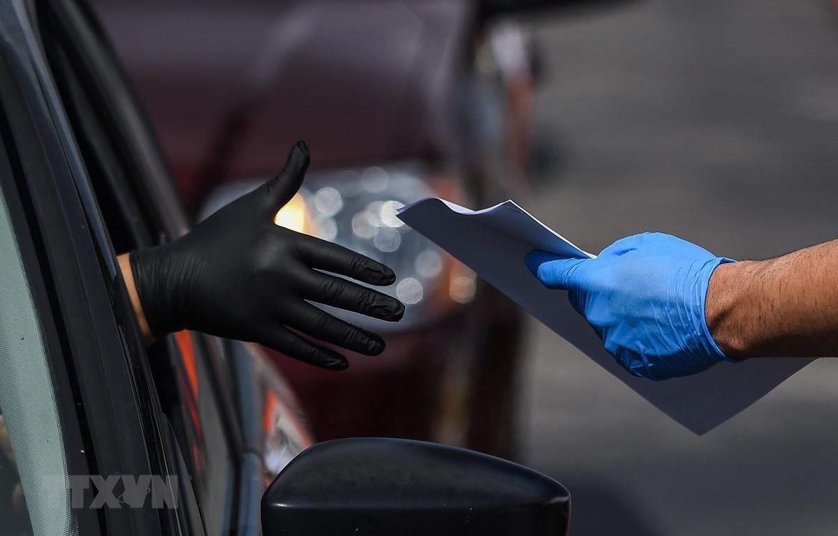 Nhận mẫu đơn xin việc làm tại một trạm lưu động để phòng lây nhiễm COVID-19 tại Hialeah, Florida, Mỹ, ngày 8/4 vừa qua. (Ảnh: AFP/TTXVN)