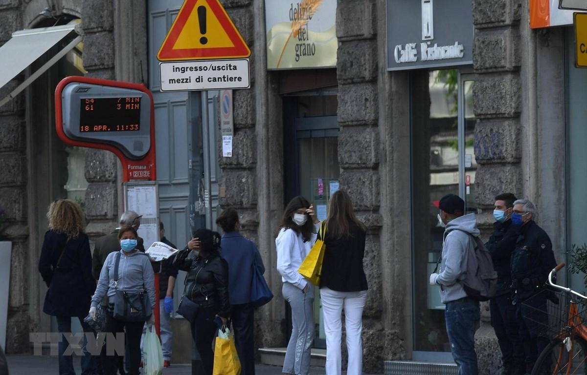 Người dân đợi xe buýt tại bến xe ở Milan, Italy ngày 18/4/2020 trong bối cảnh dịch COVID-19 đang hoành hành. Ảnh: THX/TTXVN