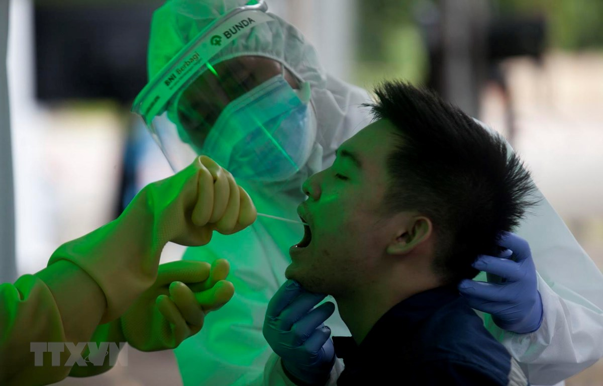 Nhân viên y tế lấy mẫu dịch xét nghiệm COVID-19 cho người dân tại Jakarta, Indonesia, ngày 20/5. (Ảnh: THX/TTXVN)