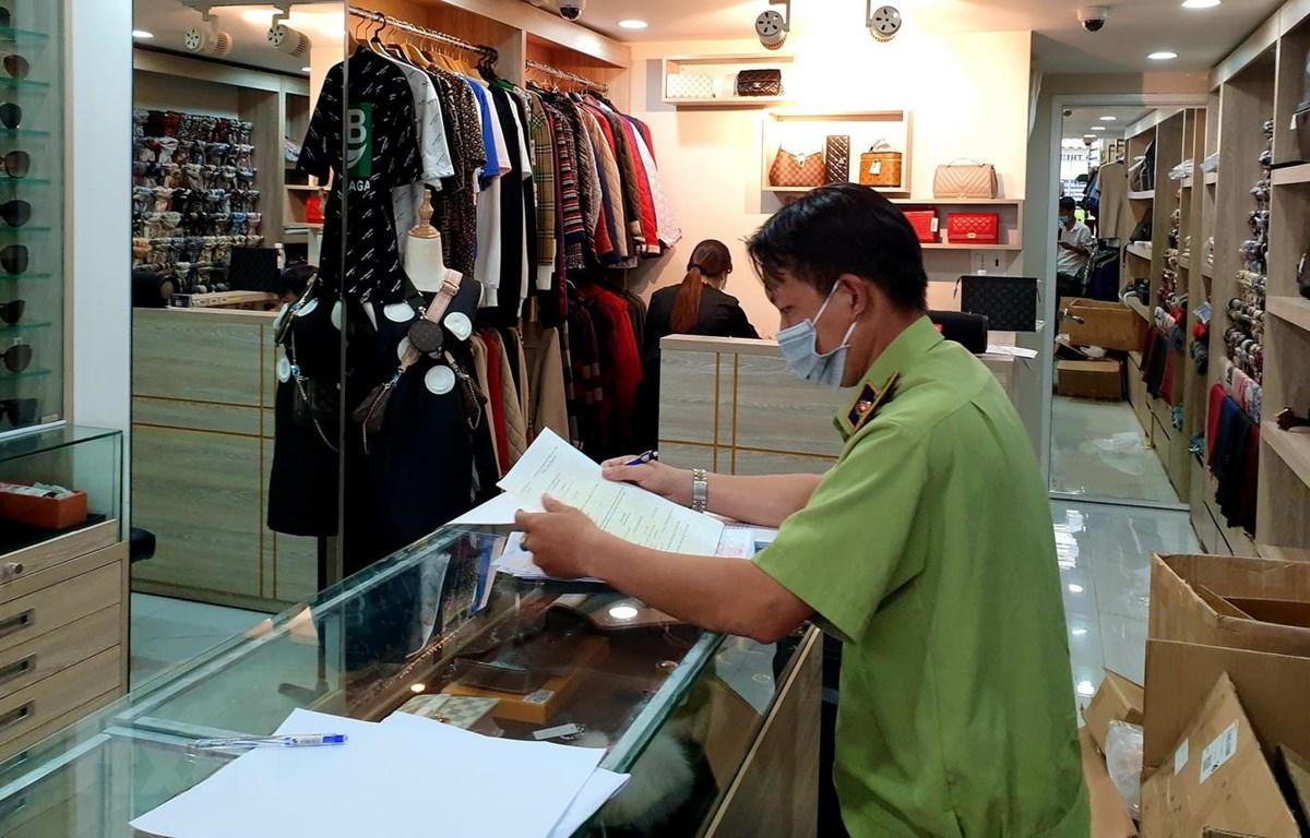 Lực lượng chức năng kiểm tra tại một cửa hàng phụ kiện thời trang ở quận 10. (Ảnh: Thành Chung/TTXVN)