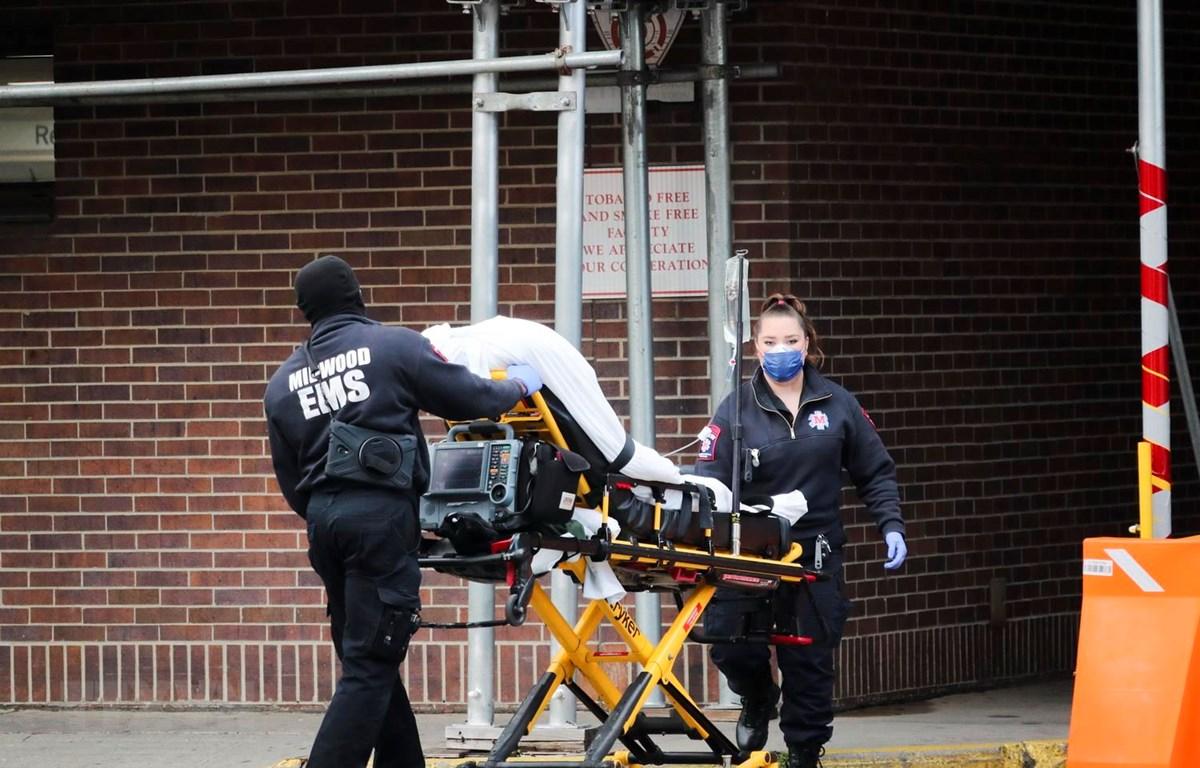 Nhân viên y tế chuyển bệnh nhân mắc COVID-19 vào một bệnh viện ở New York, Mỹ. (Ảnh: THX/TTXVN)