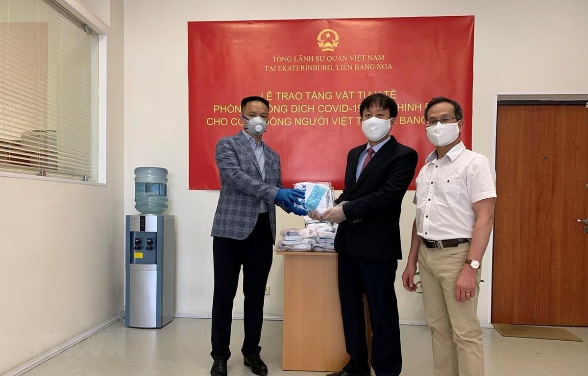 Tổng Lãnh sự Việt Nam tại thành phố Ekaterinburg Ngô Phương Nghị (giữa) trao tặng khẩu trang cho Hội người Việt Nam tỉnh Sverdlovsk. (Ảnh: TTXVN phát)