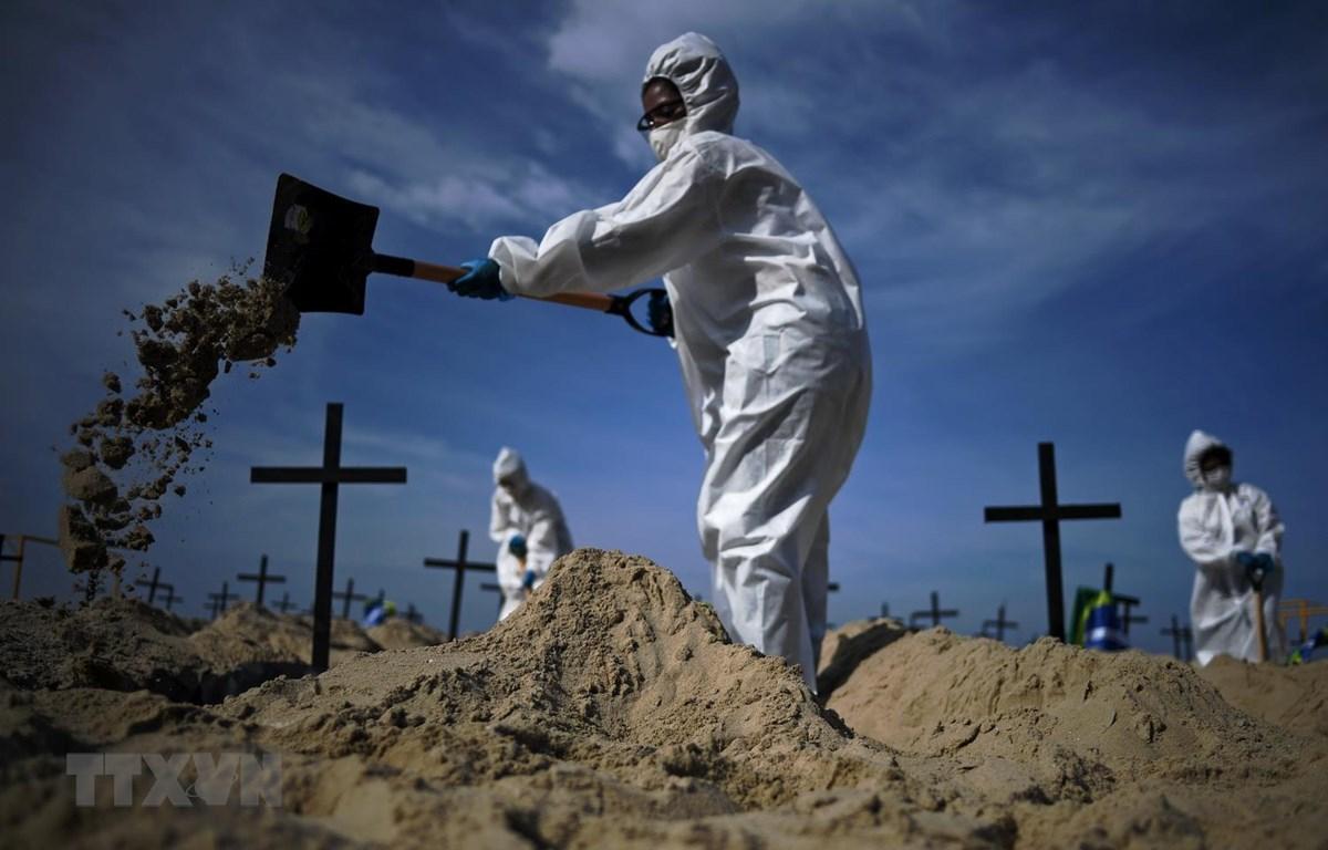 Nhóm tình nguyện đào huyệt mộ giả trên bãi biển Copacabana,để tưởng nhớ những người đã tử vong vì dịch bệnh viêm đường hô hấp cấp COVID-19 tại Rio de Janeiro, Brazil, ngày 11/6. (Ảnh: AFP/TTXVN)