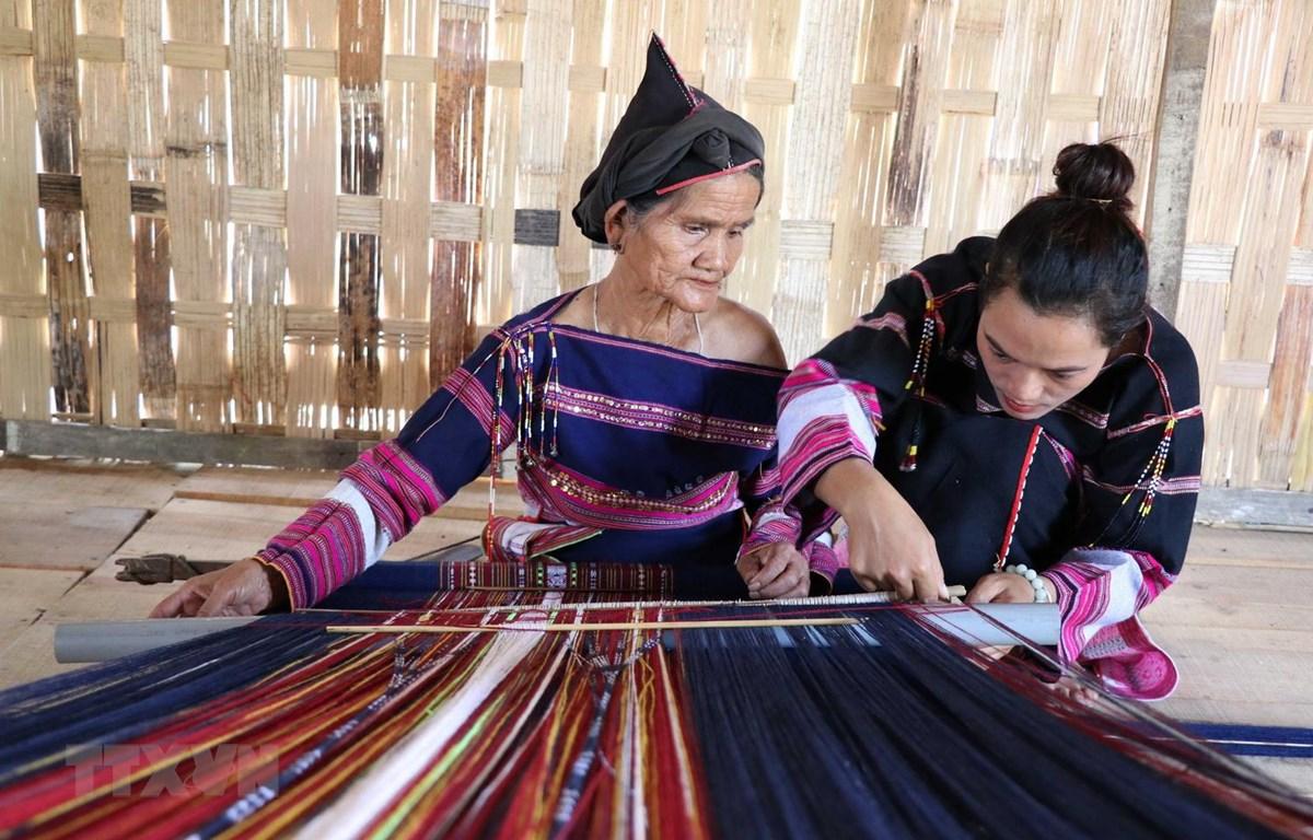 Chị Hồ Thị Viên (bên phải) cùng một nghệ nhân lớn tuổi hoàn thành sản phẩm thổ cẩm tại làng dệt Pơ Nang, xã Tú An, thị xã An Khê, tỉnh Gia Lai. (Ảnh: Hồng Điệp/TTXVN)