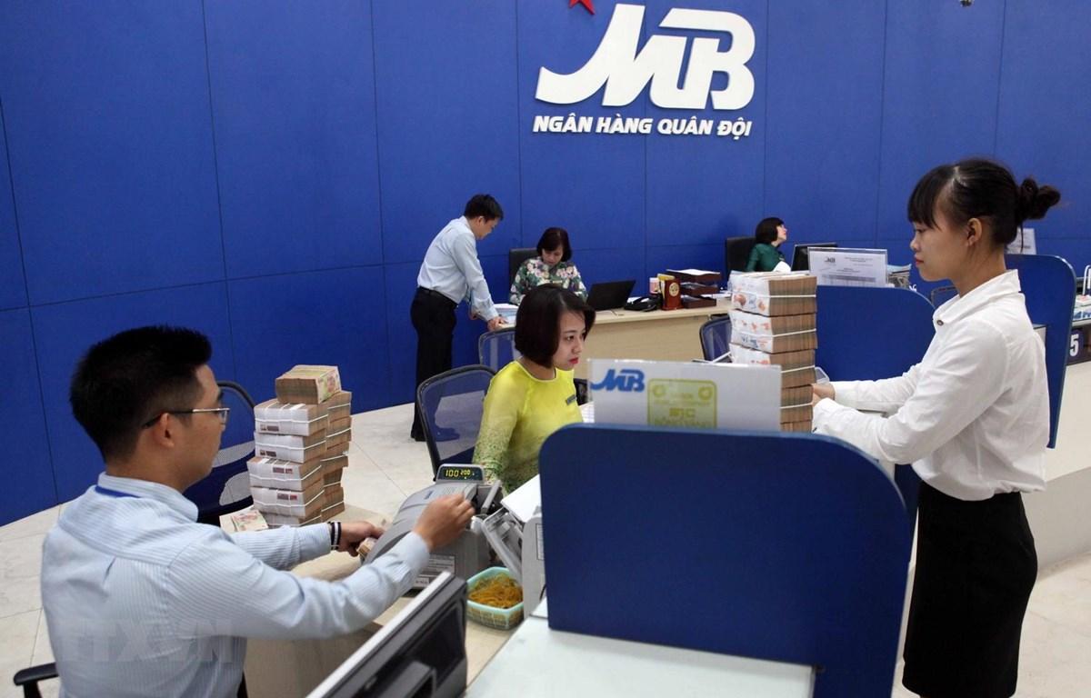 Khách hàng giao dịch tại Hội sở chính Ngân hàng TMCP Quân đội (MB) ở Hà Nội. (Ảnh: Trần Việt/TTXVN)