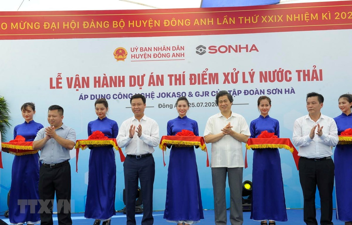 Các đại biểu thực hiện nghi thức cắt băng vận hành hệ thống xử lý nước thải thông minh. (Ảnh Mạnh Khánh/TTXVN)
