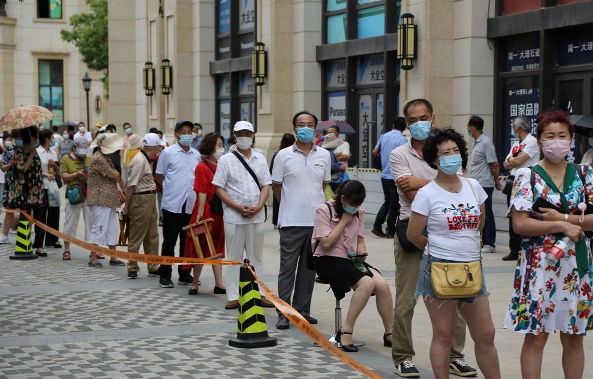 Người dân xếp hàng chờ lấy mẫu xét nghiệm COVID-19 tại thành phố Đại Liên, tỉnh Liêu Ninh, Trung Quốc ngày 28/7. (Ảnh: AFP/TTXVN)