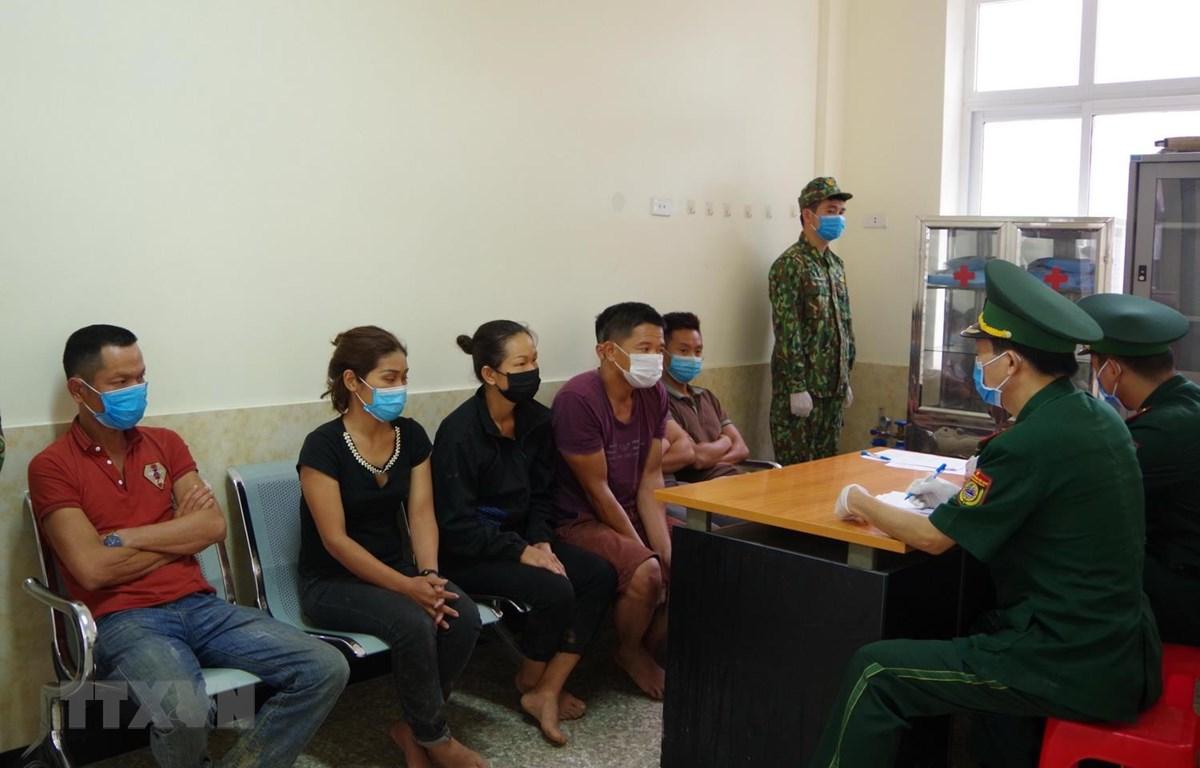 Cán bộ Biên phòng cửa khẩu Tân Thanh, Lạng Sơn lấy lời khai các đối tượng nhập cảnh trái phép ngày 1/8. (Ảnh: Quang Duy/TTXVN)