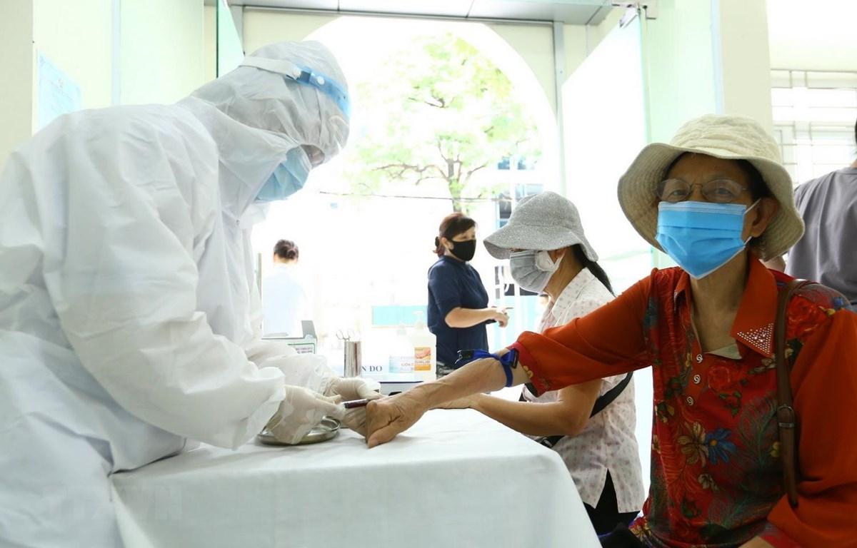 Lực lượng y tế lấy mẫu xét nghiệm nhanh cho người về từ Đà Nẵng tại phường Bách Khoa và phường Cầu Dền, quận Hai Bà Trưng, sáng 01/8. (Ảnh: Minh Quyết/TTXVN)