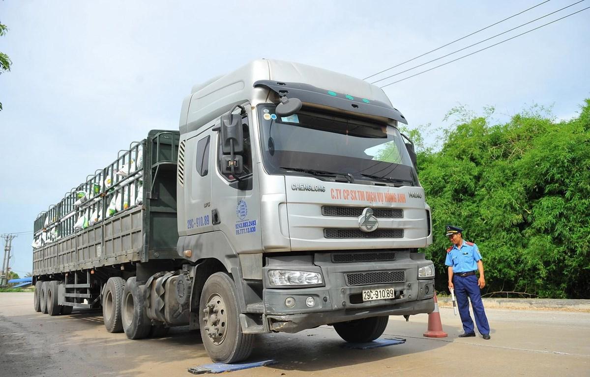 Thanh tra giao thông tỉnh Ninh Bình kiểm tra trọng tải xe tải chở hàng tại cảng. (Ảnh: Minh Đức/TTXVN)